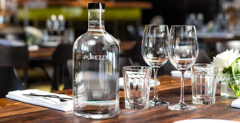 Purezza sparkling water bottle on a table at a restaurant next to wine glasses